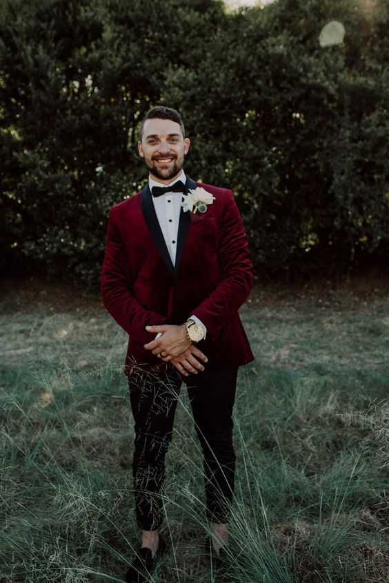 a chic groom's outfit with a burgundy velvet blazer with black lapels, a black bow tie, black cropped pants and moccasins