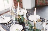 a chic tablescape with an evergreen table runner, gilded candle holders and gold rim glasses