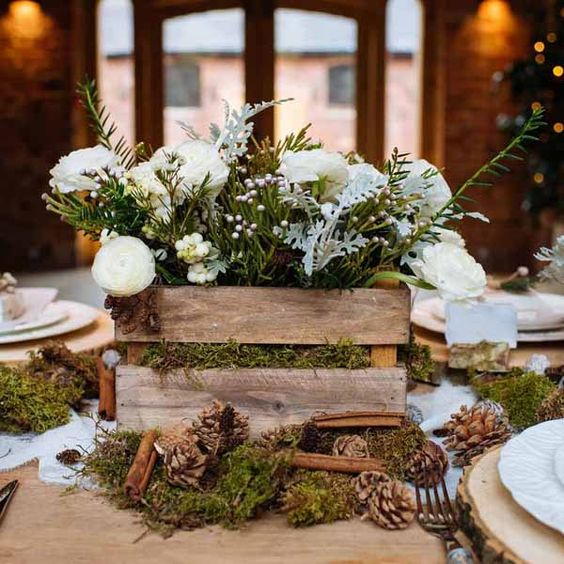 a chic winter wedding centerpiece of a crate with moss, white blooms and greenery, pinecones, cinnamon sticks and moss around