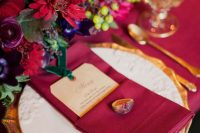 a colorful fall tablescape with marsala linens, bold red and marsala blooms, gold cutlery and gold rimmed glasses
