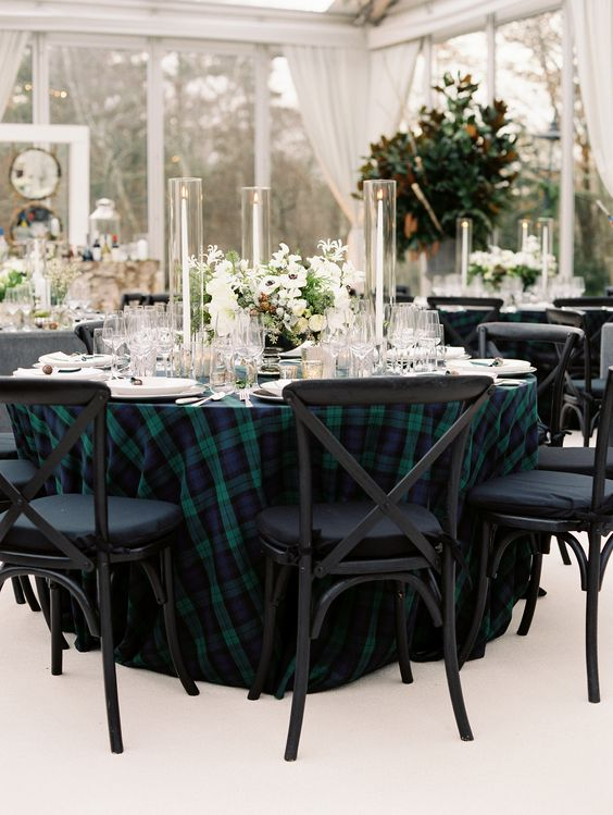 a dark tartan tablecloth paired with white blooms and greenery and with white candles for a refined wedding reception