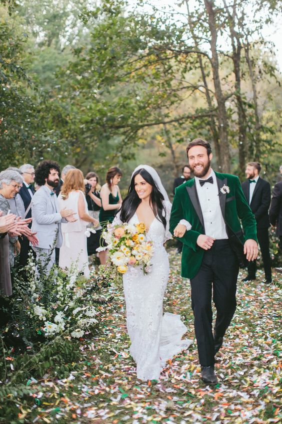 a fall groom's look with black pants, a white shirt, an emerald velvet tux with black lapels and black shoes