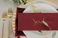 a fresh wedding tablescape with a lush greenery runner, gold cutlery and a charger, a marsala napkin and a card