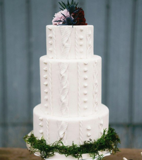 a fun winter bridal shower cake looking as a sweater and topped with bold blooms and thistles