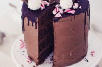 a gingerbread cake with dark chocolate dripping, crushed candy canes, Raffaello candies and glazed cookies on top