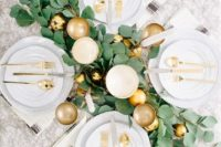 a glam tablescape with a foliage table runner, gold ornaments and cutlery plus goblets looks very festive-like