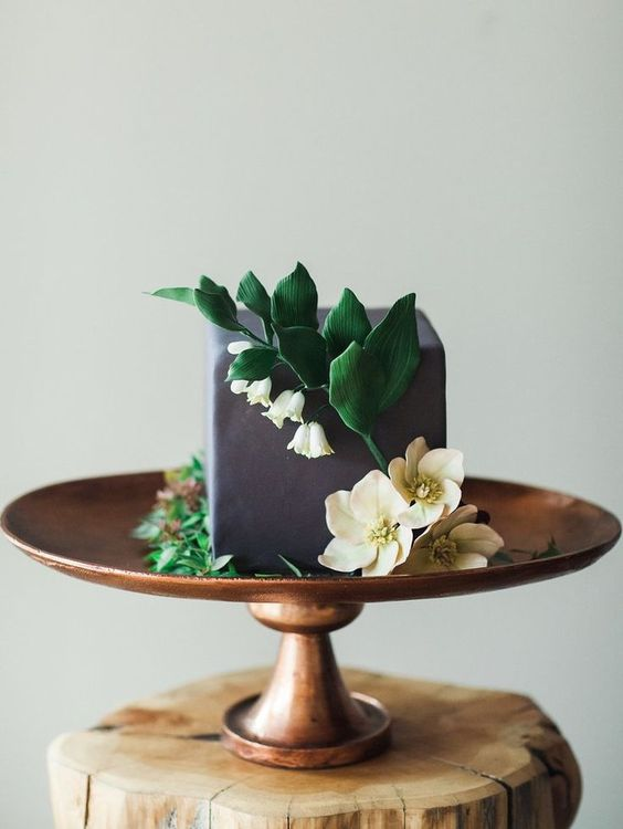 a grey square buttercream wedding cake decorated with sugar blooms and leaves is a catchy and unusual idea