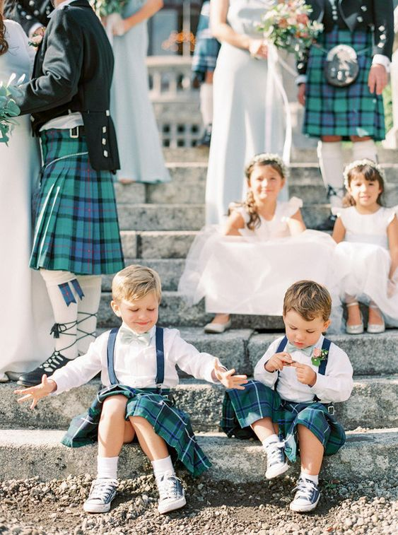 a groom, groomsmen and ring bearers all wearing green tartan kilts to commemorate the heritage of the groom