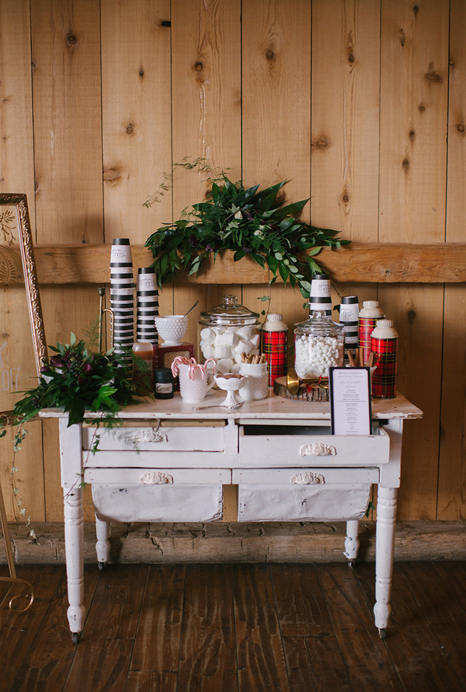 a hot cocoa bar done with greenery, plaid thermoses and delicious sweets is amazing for a Christmas wedding