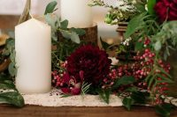 a lovely wedding tablescape with marsala blooms, berries, candles on tree stumps, greenery and gold touches