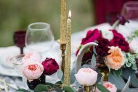 a luxurious winter wedding table with pomegranates, blush and marsala blooms, greenery and candles is chic