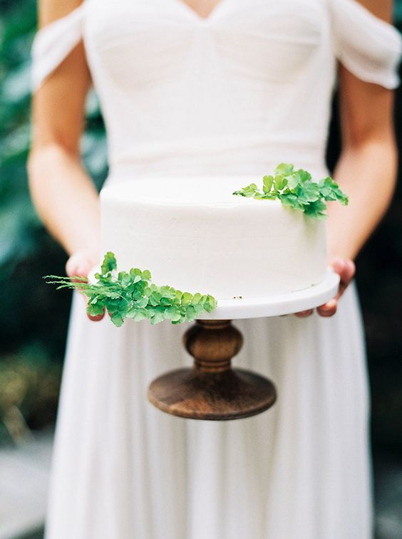 a minimal white buttercream one tier wedding cake with fresh greenery is a very stylish idea for a modern wedding