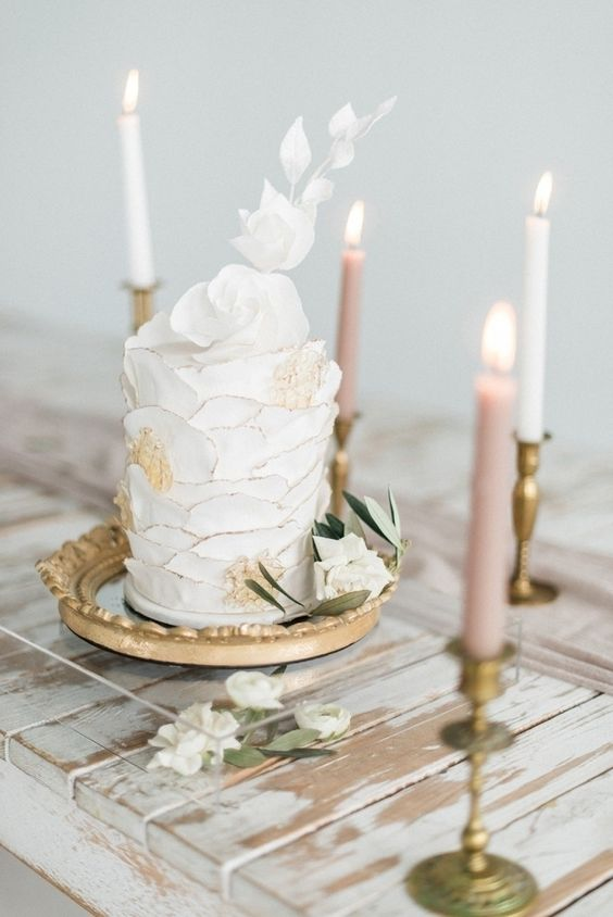 a modern and bright one tier wedding cake with textural white and gold frosting and sugar blooms on top