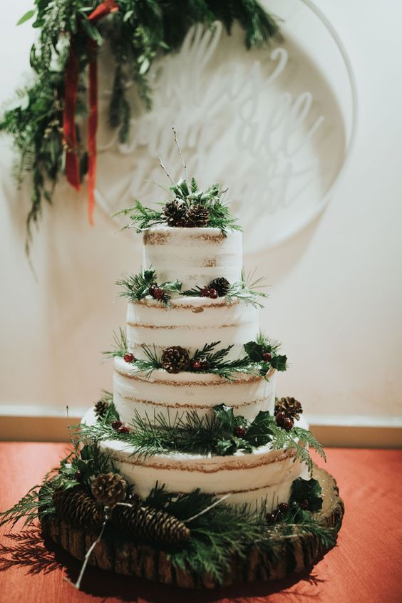 a naked wedding cake with evergreens, berries, pinecones and twigs looks wild and all-natural