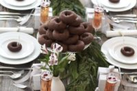 a natural tablescape with a fresh greenery runner, silver trees, chocolate donuts to make each place setting