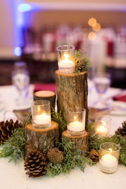 a natural wedding centerpiece of moss and evergreens, tree stumps, pinecones and floating candles