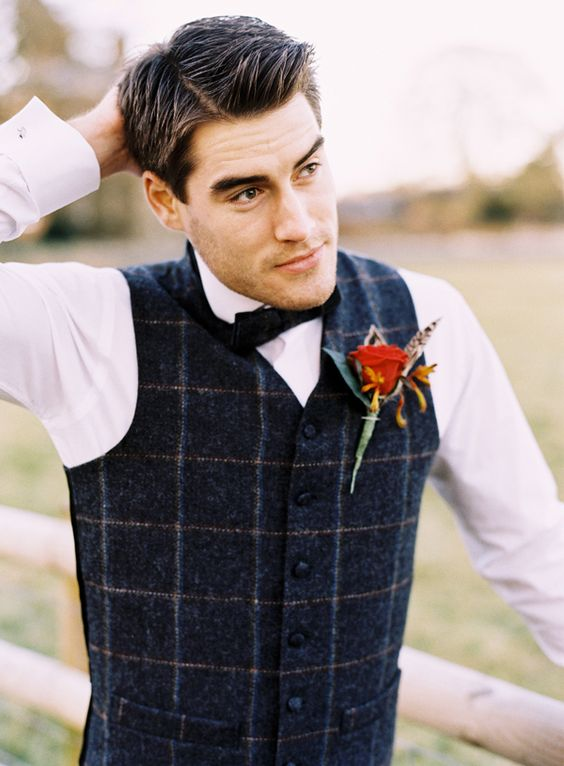 a navy plaid waistcoat, a white shirt and a black bow tie plus a red flower boutonniere are very chic