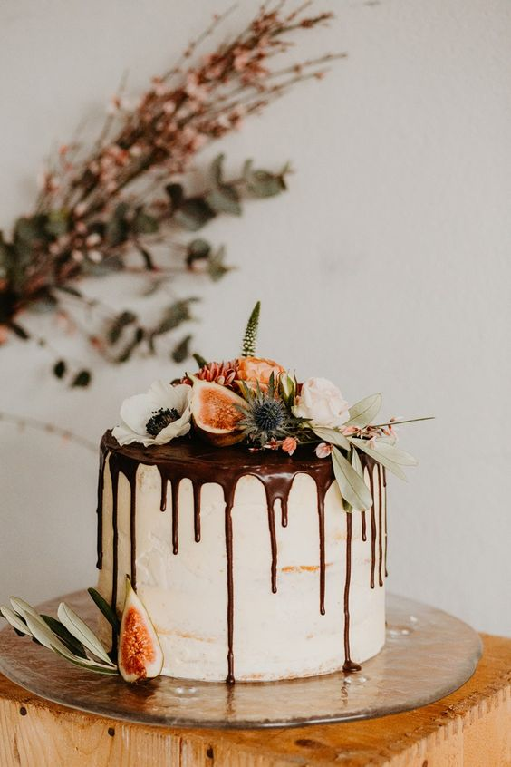 a one tier buuttercream wedding cake with chocolate drip, fresh blooms, greenery and figs on top