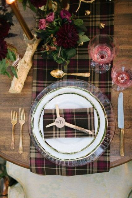 a plaid table runner and a napkin, red glasses, burgundy blooms and dark candles for a chic wedding tablescape