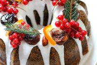 a poppy seed bundt cake with white chocolate drip, cranberries, evergrenes, cinnamon and candied fruit