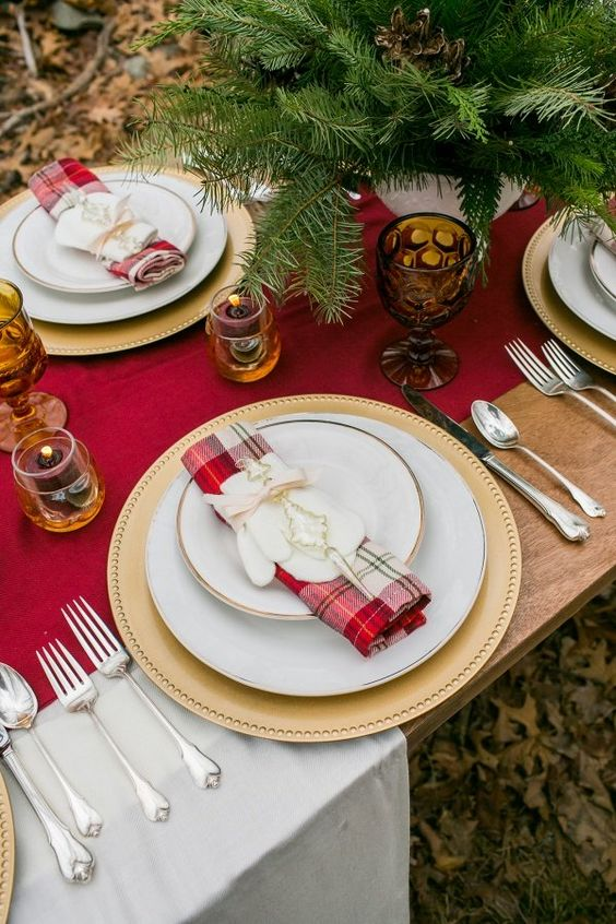a red table runner and a red plaid napkin, candles, fir branches and elegant cutlery for a Christmas wedding