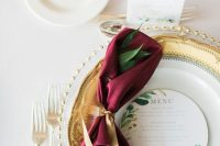 a refined and elegant wedding table setting accented with a marsala apkin and red berries looks perfect for a fall wedding