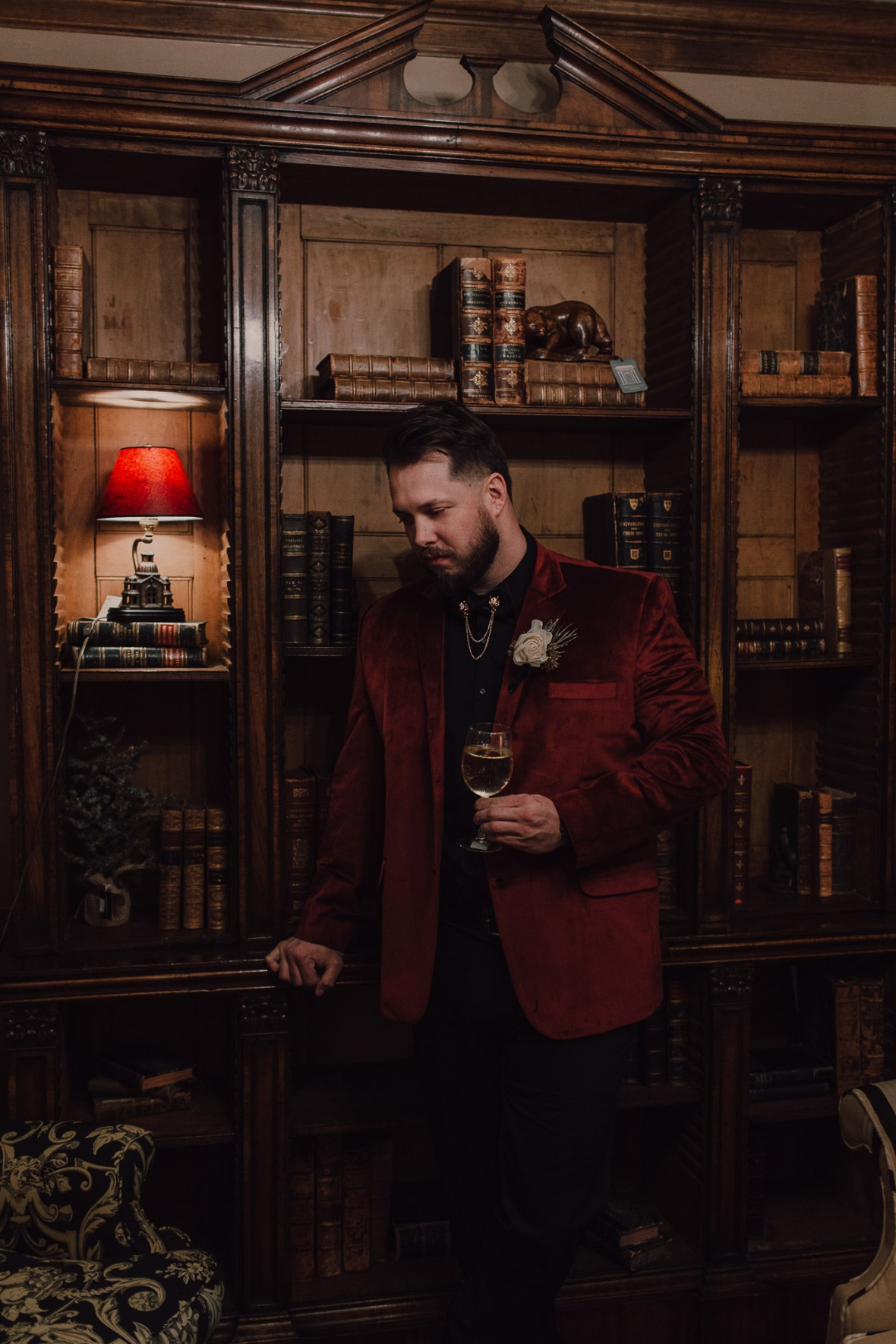 a refined groom's outfit with a black shirt, black pants, a burgundy velvet blazer and a collar chain accessory