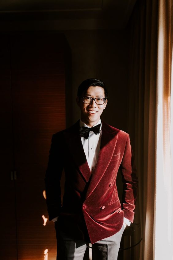 a refined groom's outfit with a burgundy velvet blazer, a black bow tie and grey pants for a fall or winter wedding
