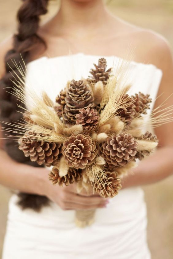 a rustic wedding bouquet of pinecones and wheat is cool for a fall or winter wedding