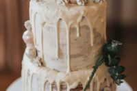 a semi naked cake with creamy drip, fresh eucalyptus and geo candies is a cool idea for a winter bridal shower