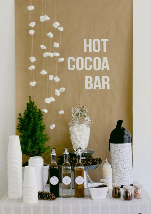 a simple hot cocoa bar with syrups, thermoses, cups and a mini tree plus marshmallows hanging over the bar