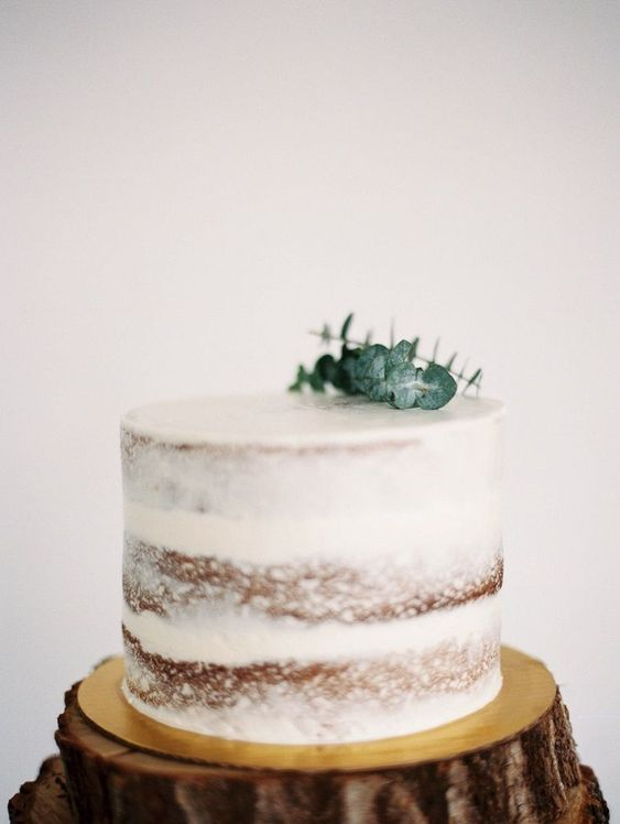 a simple single layered naked wedding cake topped with fresh eucalyptus for a minimalist wedding