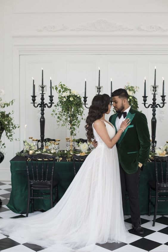 a sophisticated green velvet tux with light green lapels, a black bow tie and black pants