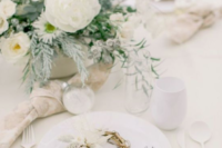a stylish frozen tablescape with white blooms and greenery, mini wreaths with feathers and white porcelain and cutlery