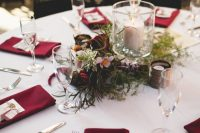 a stylish modern wedding tablescape with marsala napkins, greenery, marsala and pink blooms and candles is very chic