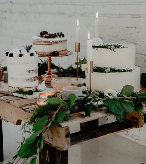 a stylish winter bridal shower dessert table with several white cakes topepd with berries and greenery and decorated with candles