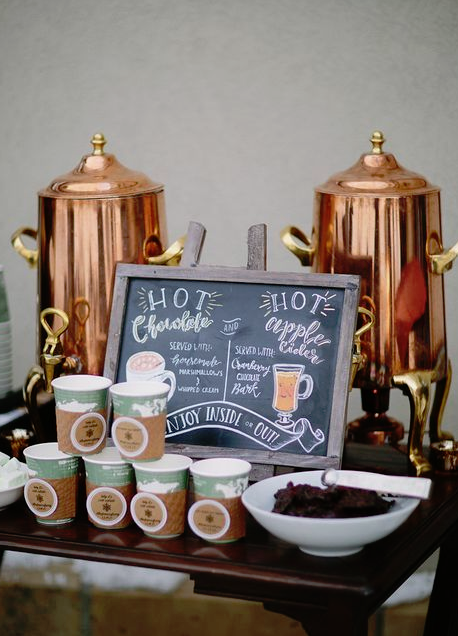 a stylish winter bridal shower hot drink station with copper tanks and cups with marks