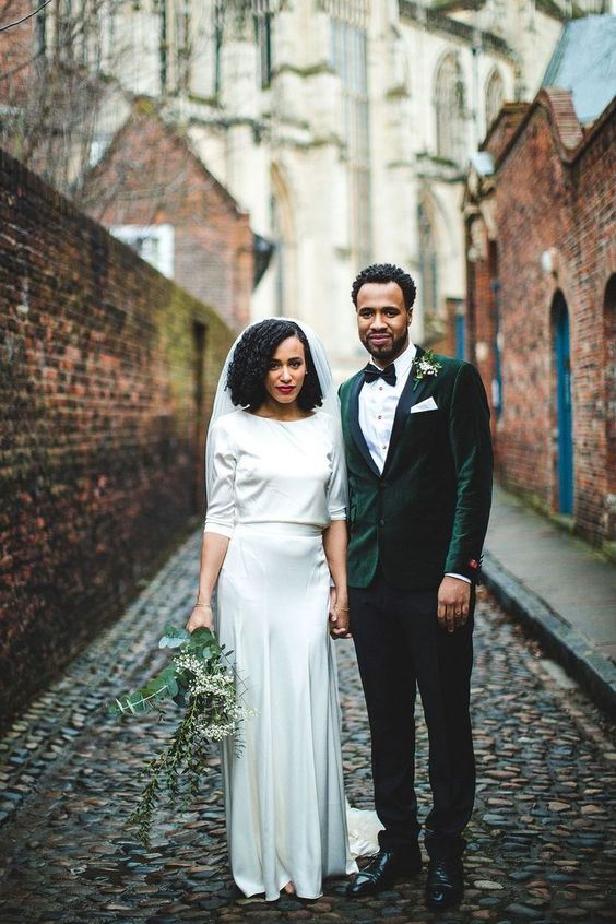 a stylish winter groom's look with a green velvet blazer, black pants, a black bow tie and a floral boutonniere