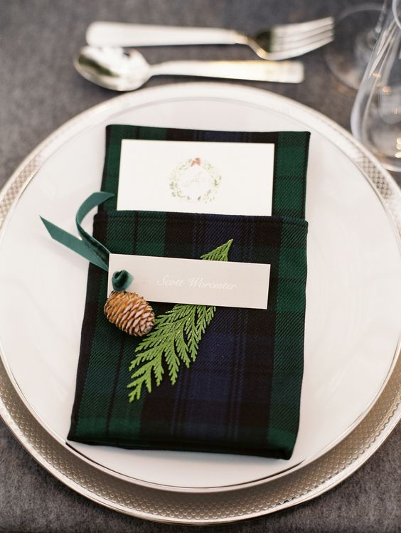a tartan napkin pocket with a pinecone and fern is a stylish idea to decorate your wedding tablescape