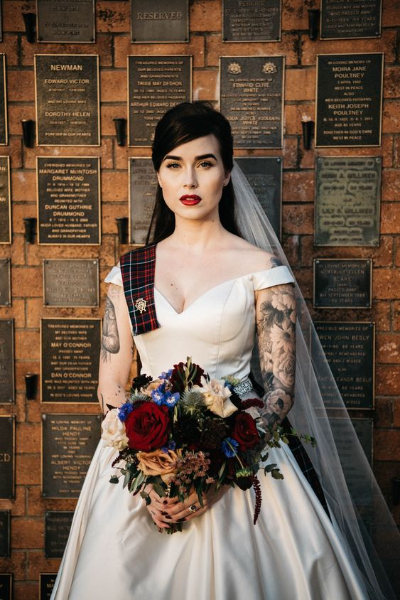 a tartan ribbon with a brooch attached to the wedding dress is a cool statement for a bridal look