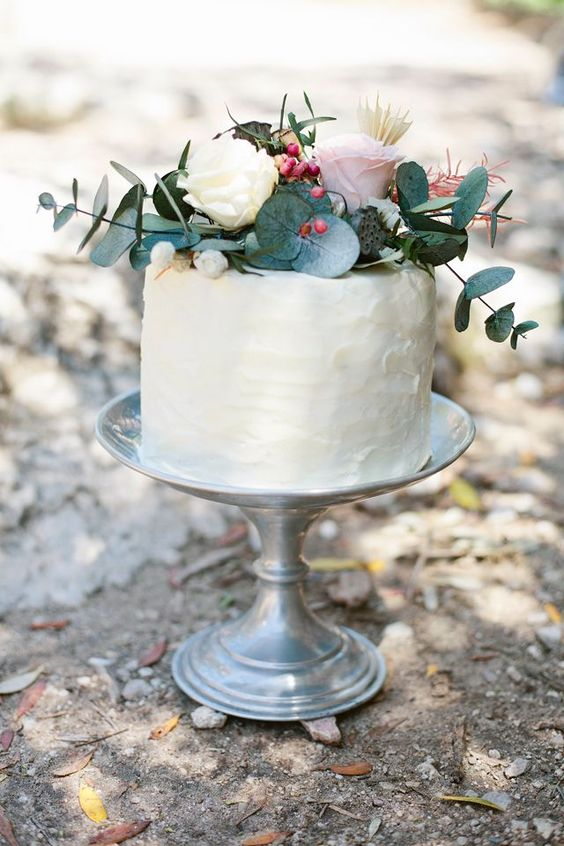 a textural buttercream one tier wedding cake with greenery and fresh blooms on top for a romantic wedding