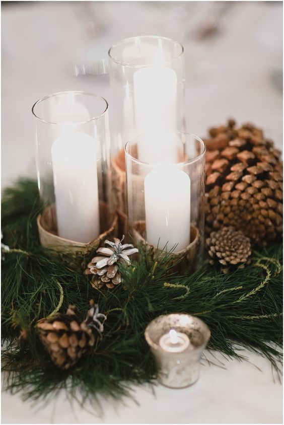 a warming winter wedding centerpiece of evergreens, pinecones, pillar candles and mercury glass candleholders