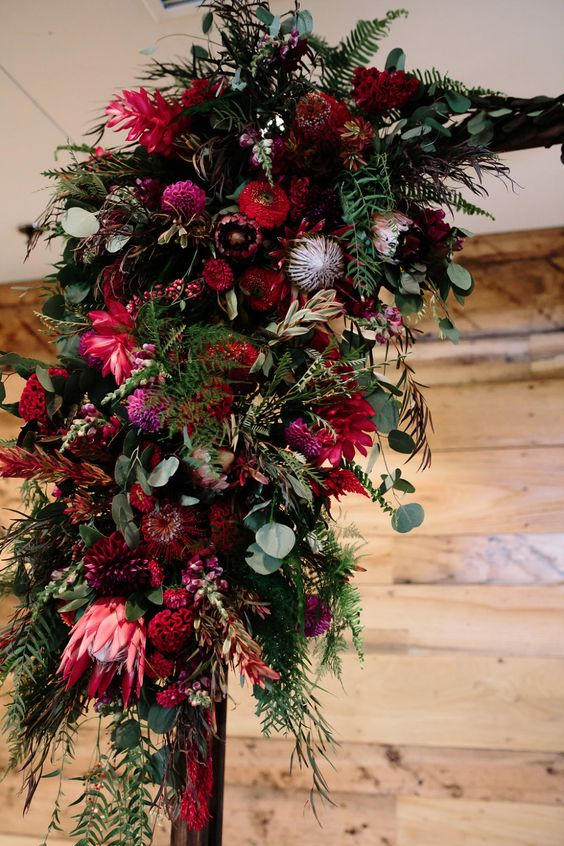 a wedding arch with red, marsala and pink blooms, greenery, foliage and neutral blooms is a lovely idea to rock