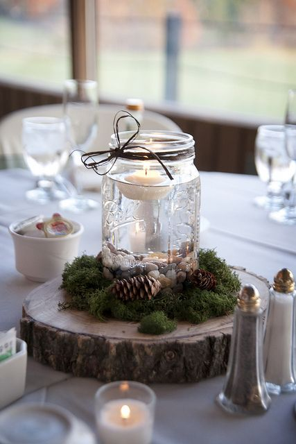 a wedding centerpiece of a wood slice with moss, pinecones and a jar with pebbles and a floating candle