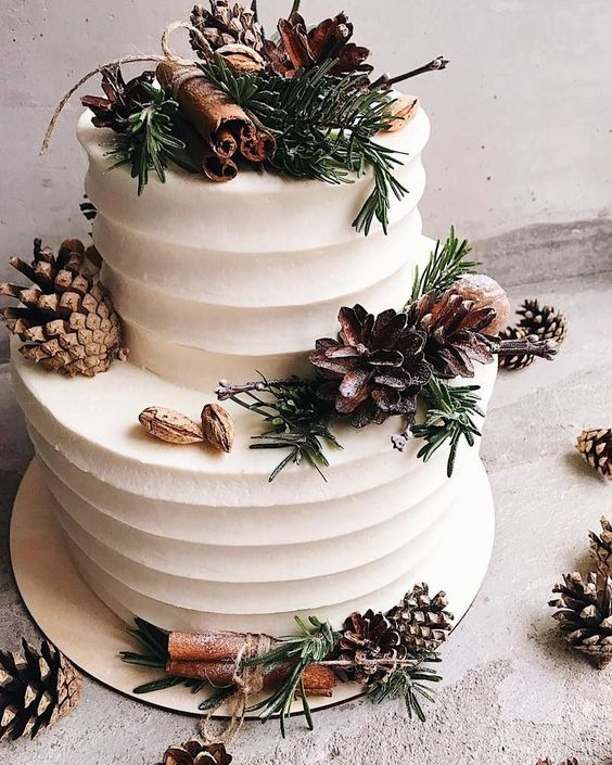 a white textural winter wedding cake with pinecones, evergreens, cinnamon sticks, nuts and other stuff