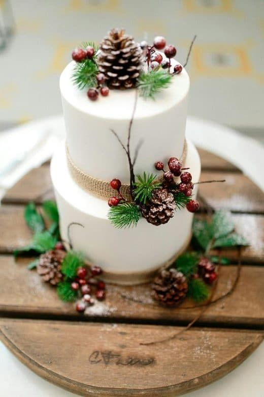 a white wedding cake decorated with burlap, berries, pinecones, twigs and evergreens for a winter wedding