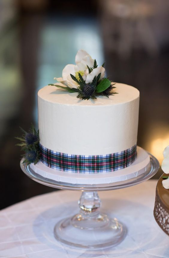 a white wedding cake with a tartan ribbon, thistles and white blooms on top is a stylish and bold idea