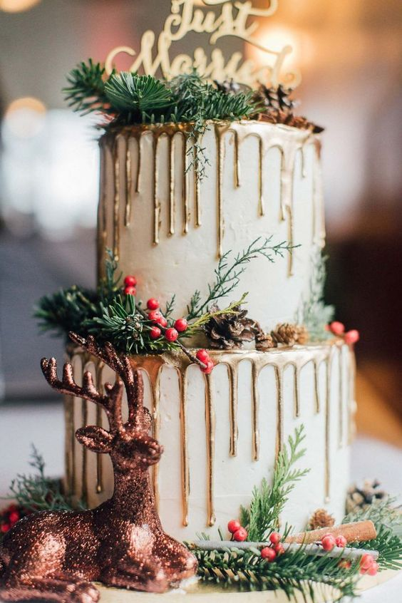 a white winter wedding cake with gold drip, pinecones, evergreens and berries, a calligraphy topper and a pink glitter deer