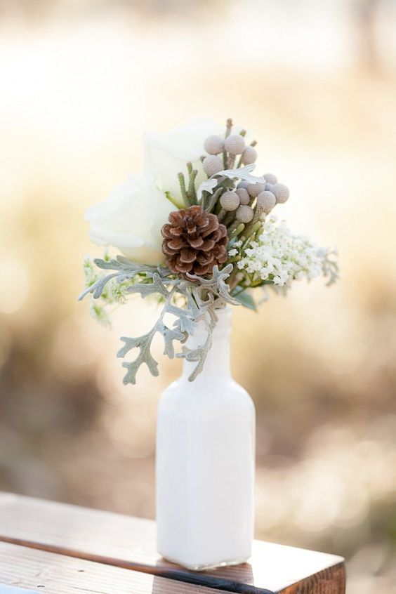 a winter wedding centerpiece of a white bottles with berries, pale greenery, white roses is a romantic decoration