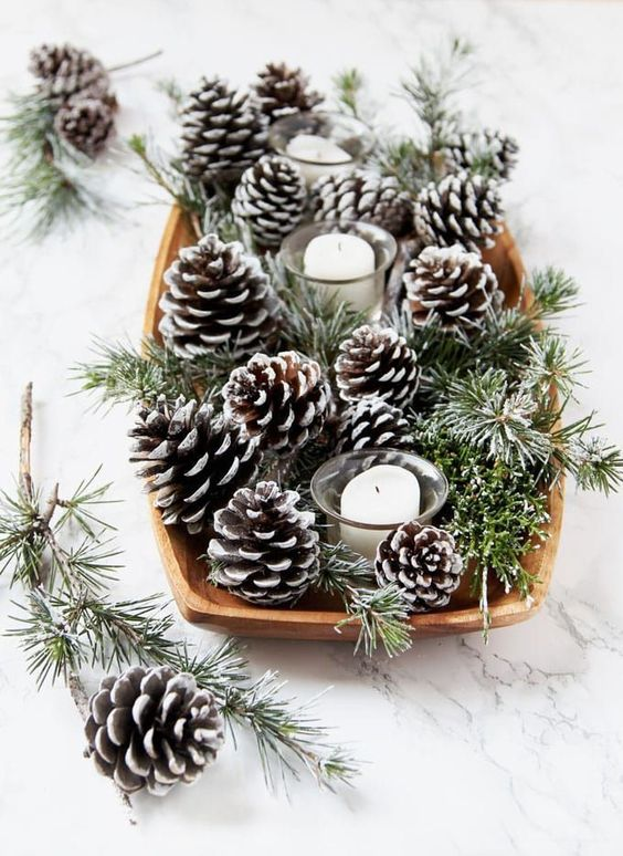 a winter wedding centerpiece of a wooden bowl with evergreens, snowy pinecones and pillar candles is lovely
